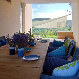 Ispirazione per un grande patio o portico mediterraneo in cortile con pedane e un tetto a sbalzo