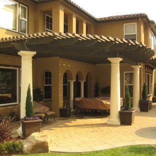 Esempio di un patio o portico mediterraneo con un focolare e una pergola
