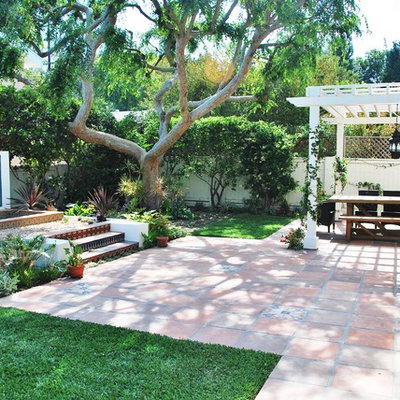 Inspiration for a mediterranean backyard tile patio fountain remodel in Los Angeles with a pergola