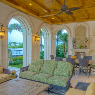 Example of a tuscan patio design in Miami with a fire pit and a roof extension