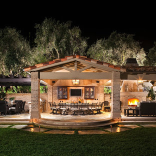 Inspiration for an expansive mediterranean back patio in Orange County with an outdoor kitchen, natural stone paving and an awning.