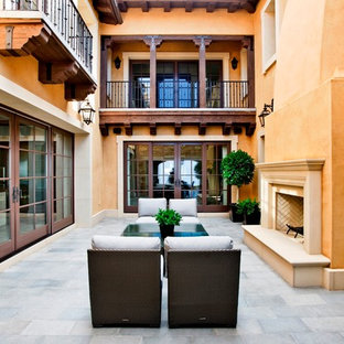 Example of a tuscan patio design in Orange County with a fire pit