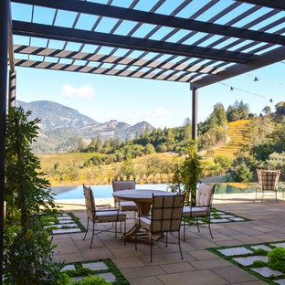 Tuscan backyard patio photo in Other with a pergola