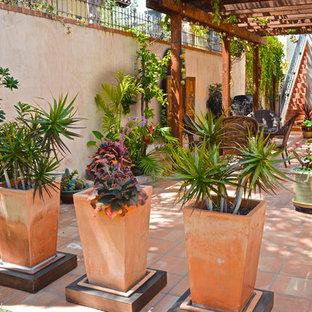 Ejemplo de patio mediterráneo con suelo de baldosas y pérgola