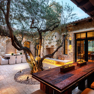 Example of a tuscan courtyard patio design in San Diego with a fire pit