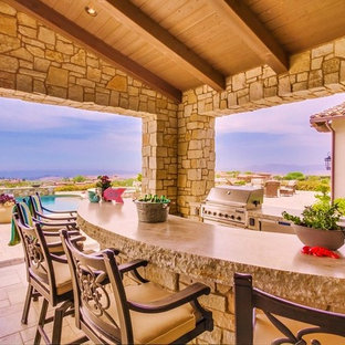 Design ideas for an expansive mediterranean back patio in San Diego with an outdoor kitchen, natural stone paving and a roof extension.