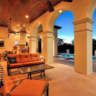 Foto di un grande patio o portico mediterraneo dietro casa con lastre di cemento e un tetto a sbalzo