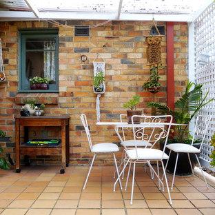 Foto di un patio o portico eclettico di medie dimensioni con un giardino in vaso, piastrelle e una pergola