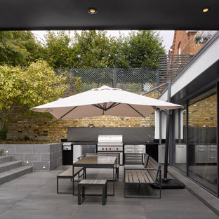 Design ideas for a medium sized contemporary back patio in London with an outdoor kitchen, concrete paving and no cover.