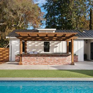 Ispirazione per un patio o portico country di medie dimensioni e dietro casa con lastre di cemento e una pergola