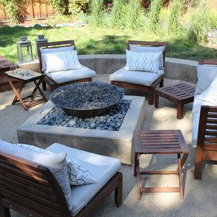 Aménagement d'une terrasse arrière contemporaine de taille moyenne avec un foyer extérieur, un gravier de granite et aucune couverture.