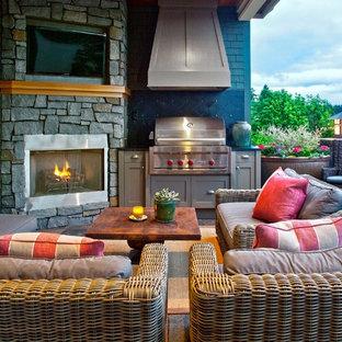 Inspiration pour une terrasse arrière traditionnelle de taille moyenne avec un foyer extérieur, une extension de toiture et des pavés en pierre naturelle.