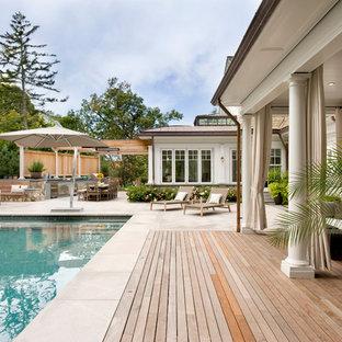 Idee per un grande patio o portico chic dietro casa con pavimentazioni in pietra naturale e una pergola