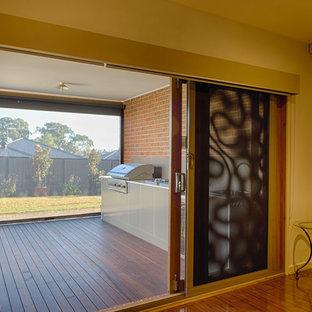 Foto di un grande patio o portico minimalista dietro casa con pedane e un tetto a sbalzo