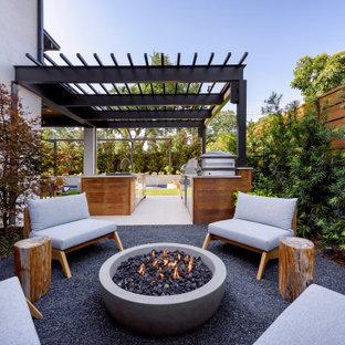 Esempio di un patio o portico minimal di medie dimensioni e dietro casa con un focolare e un tetto a sbalzo