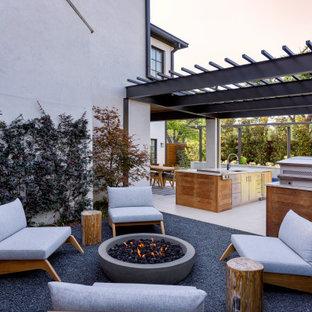 Idee per un patio o portico minimal di medie dimensioni e dietro casa con un focolare e un tetto a sbalzo
