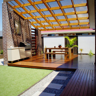 Small contemporary back patio in Brisbane with an outdoor kitchen, decking and a pergola.