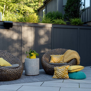 This is an example of a large midcentury backyard patio in Boston with concrete pavers and no cover.