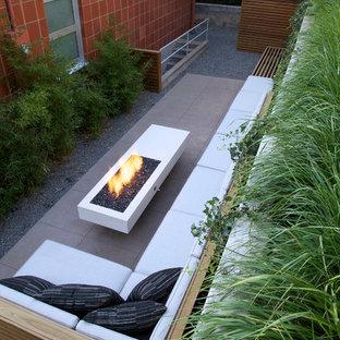 Immagine di un patio o portico moderno dietro casa e di medie dimensioni con un focolare, lastre di cemento e nessuna copertura