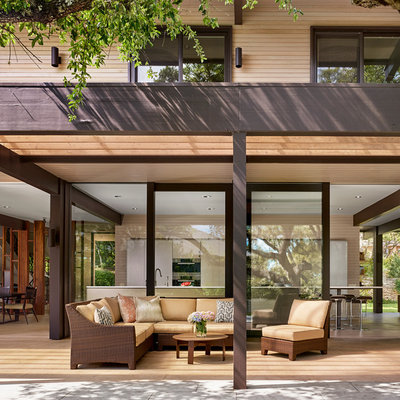 Example of a large trendy backyard patio fountain design in Austin with decking and a pergola