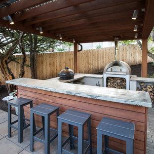 Cette photo montre une terrasse arrière rétro avec des pavés en béton et une pergola.
