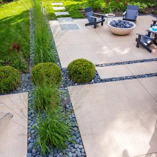 Esempio di un patio o portico moderno di medie dimensioni e dietro casa con un focolare e lastre di cemento