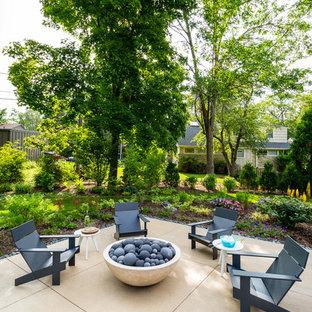 Esempio di un patio o portico design di medie dimensioni e dietro casa con un focolare e lastre di cemento