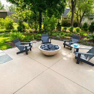 Aménagement d'une terrasse arrière moderne de taille moyenne avec un foyer extérieur et une dalle de béton.