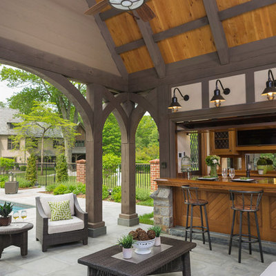 Example of a large classic backyard tile patio kitchen design in New York with a roof extension