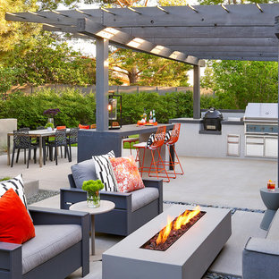 This is an example of a retro back patio in Denver with an outdoor kitchen, concrete slabs and a pergola.