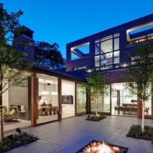 Ispirazione per un patio o portico industriale in cortile con un focolare
