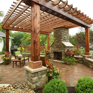 Photo of a large transitional backyard patio in Columbus with brick pavers and a pergola.
