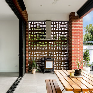 Photo of a contemporary backyard patio in Adelaide with an outdoor kitchen, concrete pavers and a roof extension.