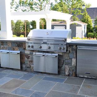 Idee per un ampio patio o portico bohémian dietro casa con pavimentazioni in pietra naturale e un tetto a sbalzo