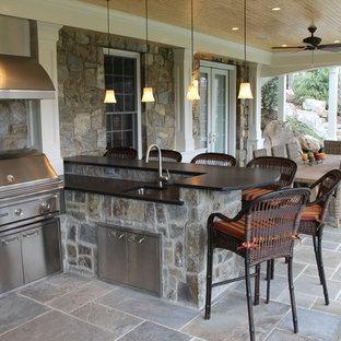 Esempio di un patio o portico stile americano di medie dimensioni e dietro casa con piastrelle e un tetto a sbalzo
