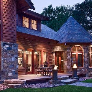 Idee per un grande patio o portico rustico dietro casa con un focolare, lastre di cemento e un tetto a sbalzo