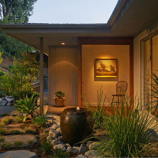 Example of a mid-sized southwest backyard stone patio fountain design in Los Angeles with a roof extension
