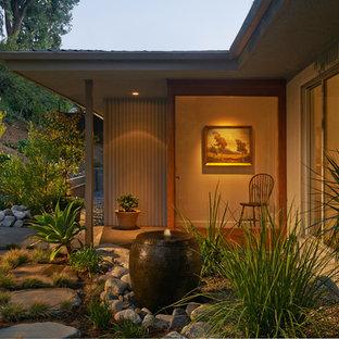 Foto di un patio o portico stile americano di medie dimensioni e dietro casa con fontane, un tetto a sbalzo e pavimentazioni in pietra naturale
