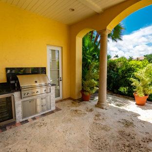 Idee per un patio o portico mediterraneo dietro casa con pavimentazioni in mattoni e un tetto a sbalzo