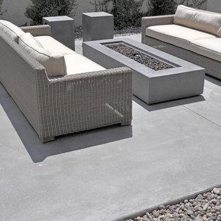 Ejemplo de patio actual, de tamaño medio, sin cubierta, en patio trasero, con fuente y losas de hormigón