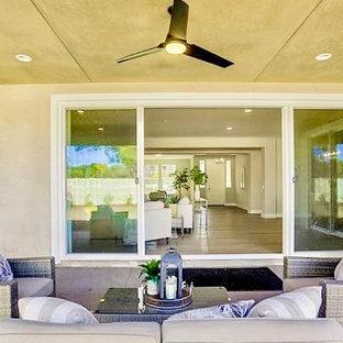 Idee per un grande patio o portico chic dietro casa con un caminetto, cemento stampato e un tetto a sbalzo