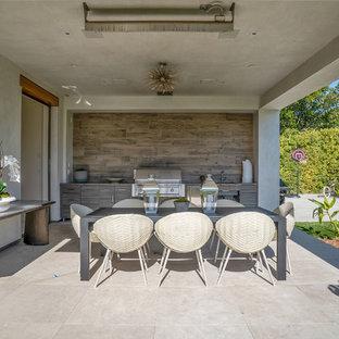 Ispirazione per un grande patio o portico design dietro casa con pavimentazioni in pietra naturale e un tetto a sbalzo