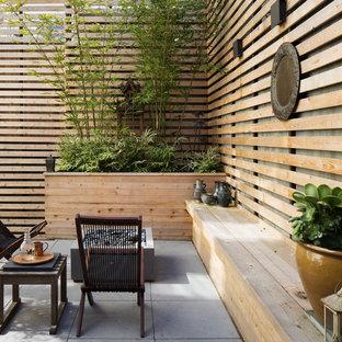 Idee per un patio o portico etnico con un focolare, pavimentazioni in cemento e nessuna copertura