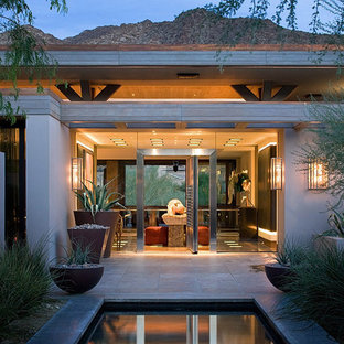 Inspiration for a contemporary patio remodel in Orange County with a roof extension