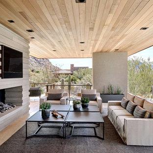 Foto di un patio o portico stile americano con un caminetto, piastrelle e un tetto a sbalzo