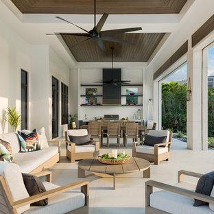 Immagine di un grande patio o portico moderno dietro casa con piastrelle e un tetto a sbalzo