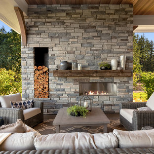 Пример оригинального дизайна: огромный дворик на заднем дворе в стиле кантри с уличным камином, покрытием из бетонных плит и навесом