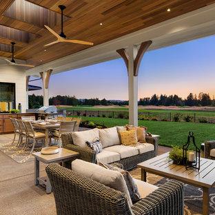 Esempio di un ampio patio o portico country dietro casa con lastre di cemento e un tetto a sbalzo