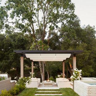 Ispirazione per un patio o portico moderno dietro casa con un focolare e una pergola