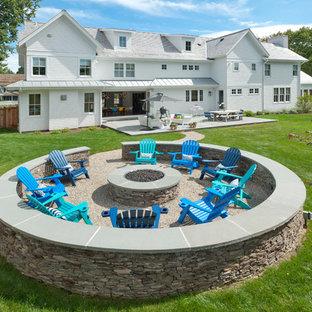 Esempio di un grande patio o portico country dietro casa con un focolare e una pergola